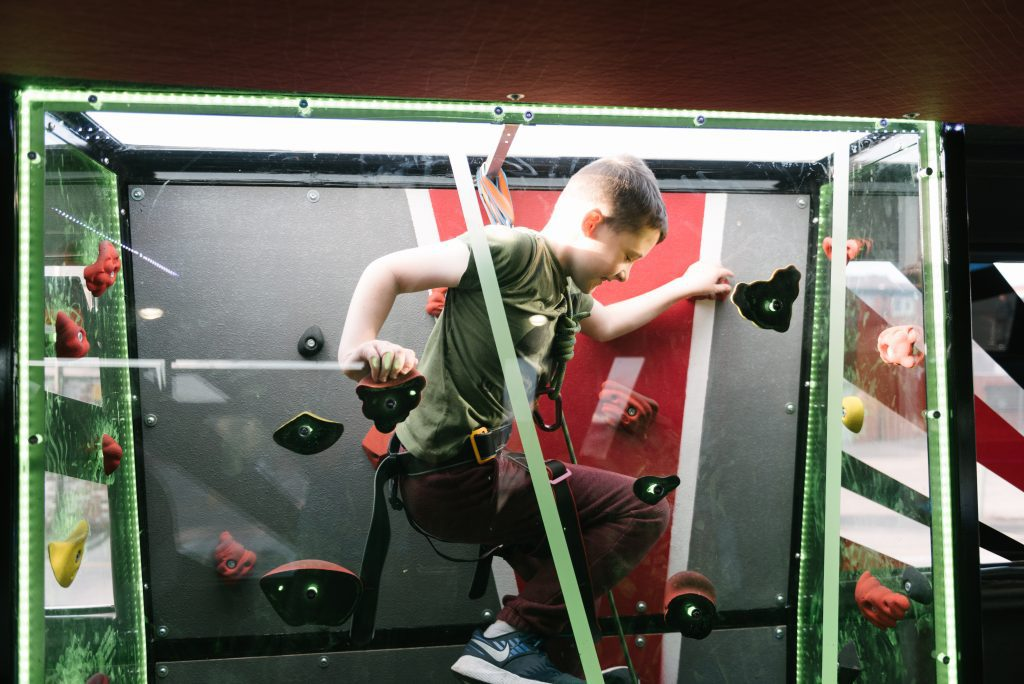 Young person having fun on a climbing wall on board the Message Bus.