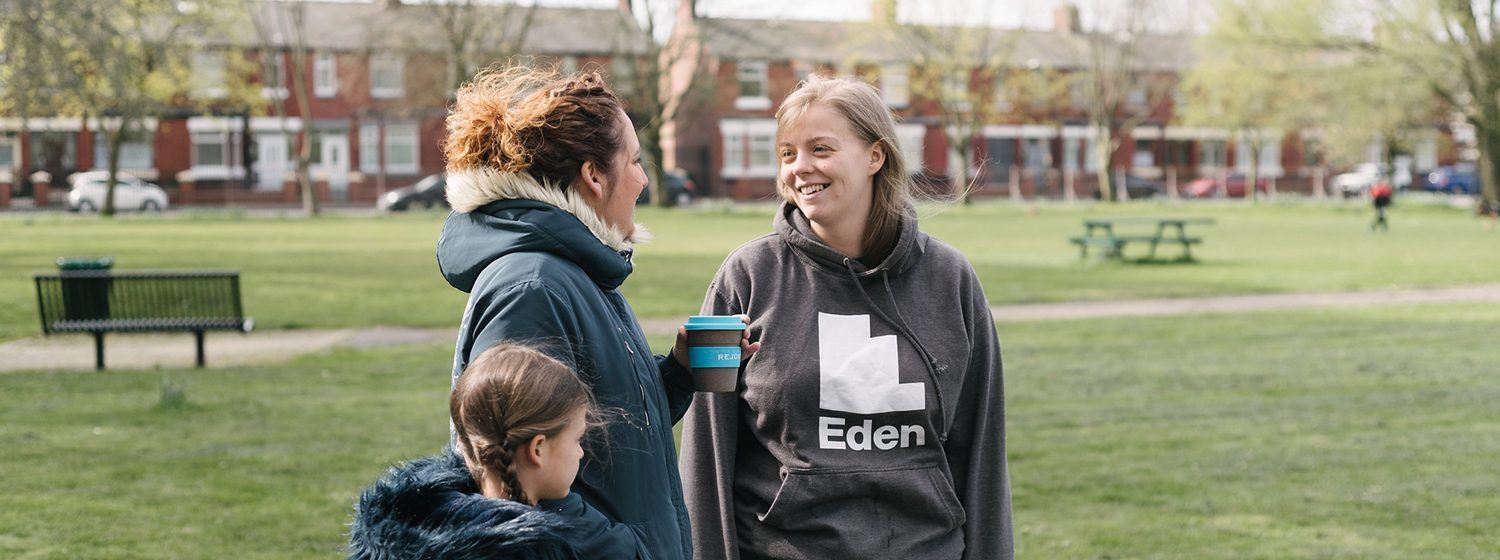 Eden team member talking to a woman and child