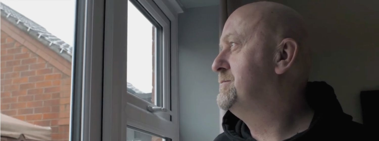 Grieving man looking out of the window